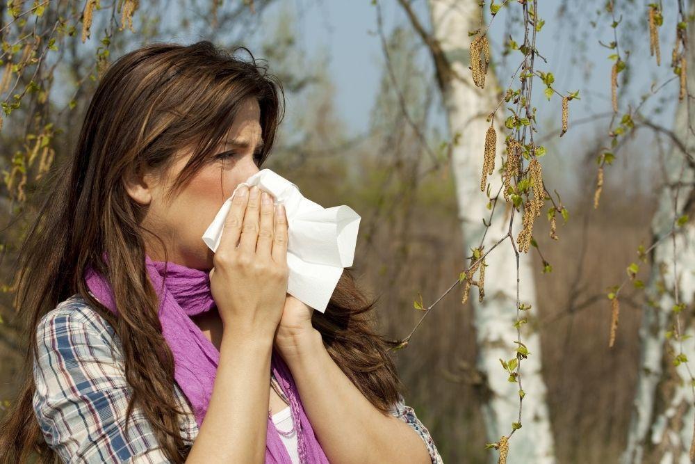 Siitepölyallergiasta kärsivä nainen niistää nenäänsä ulkona.
