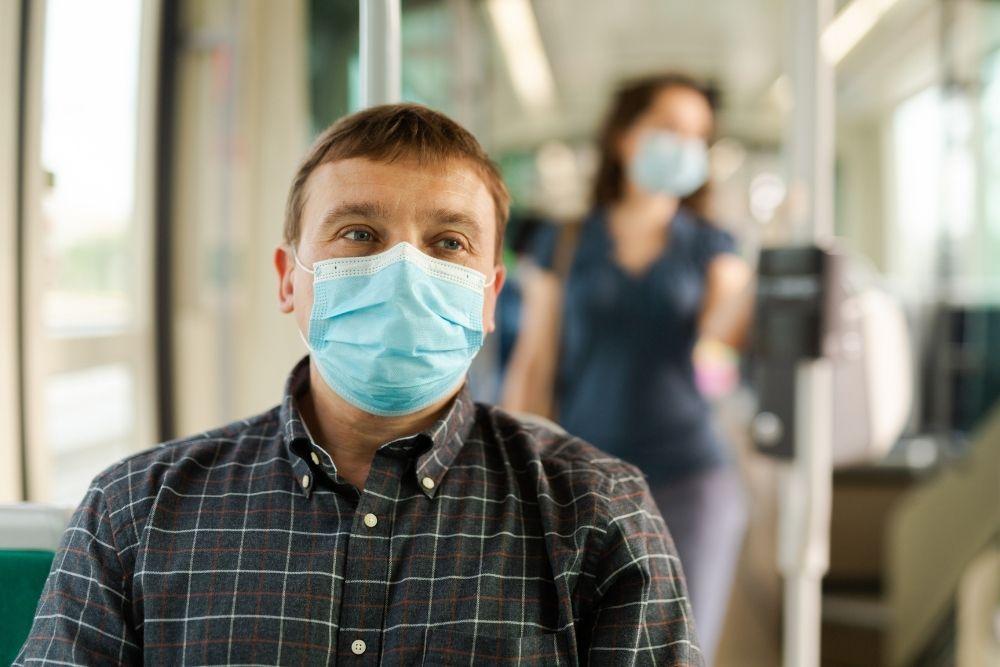 Flunssainen mies maskissa matkalla lääkäriin.