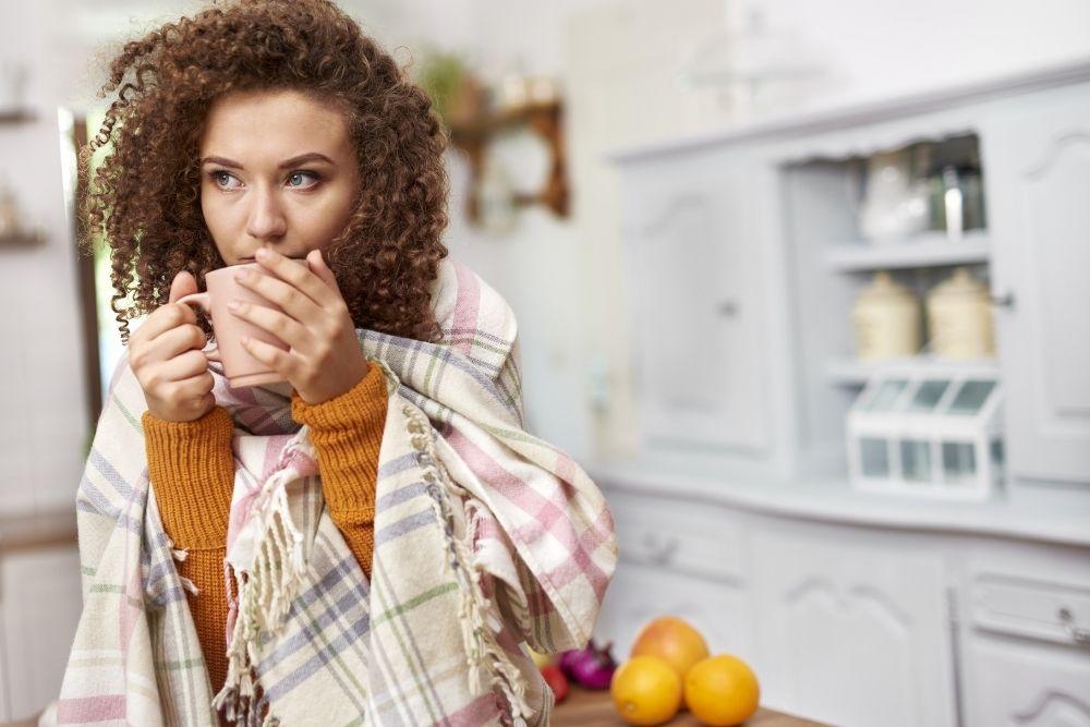 Flunssainen nainen juo teetä.