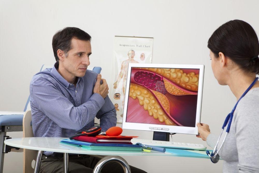 Ateroskleroosia sairastava mies katsoo lääkärin kanssa kuvaa valtimon ahtaumasta.