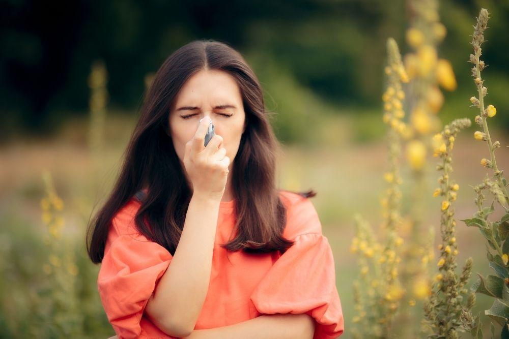 Nainen hengittää astmalääkettä