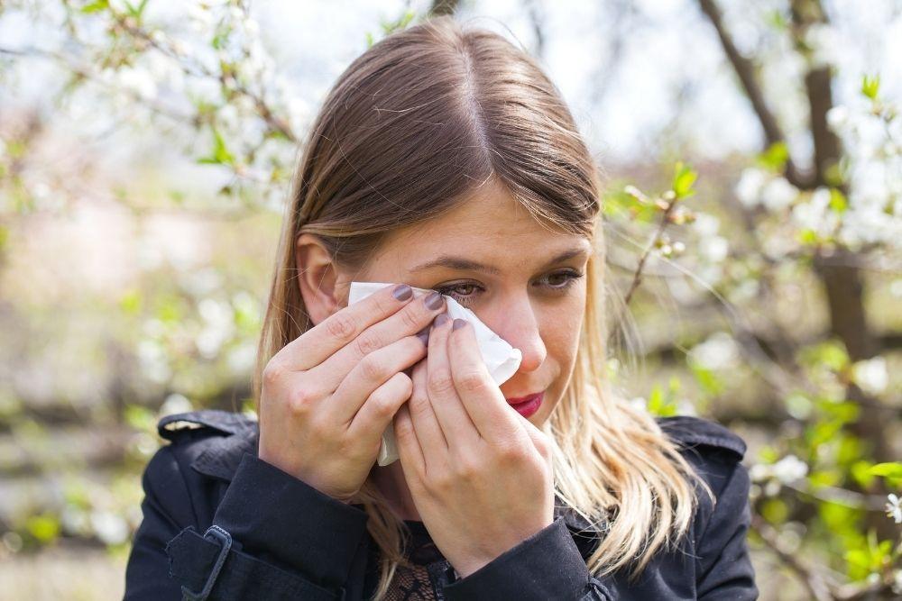 Allergisesta nuhasta kärsivä nainen pyyhkii silmiään.
