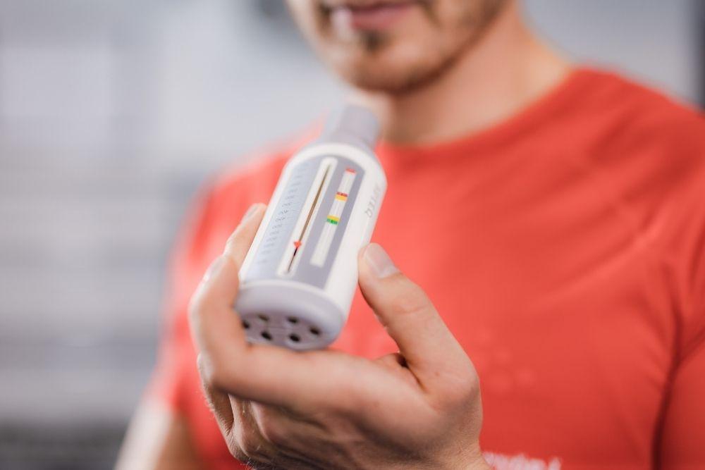 Flunssassa oleva astmaatikko pitää PEF-mittaria kädessään.