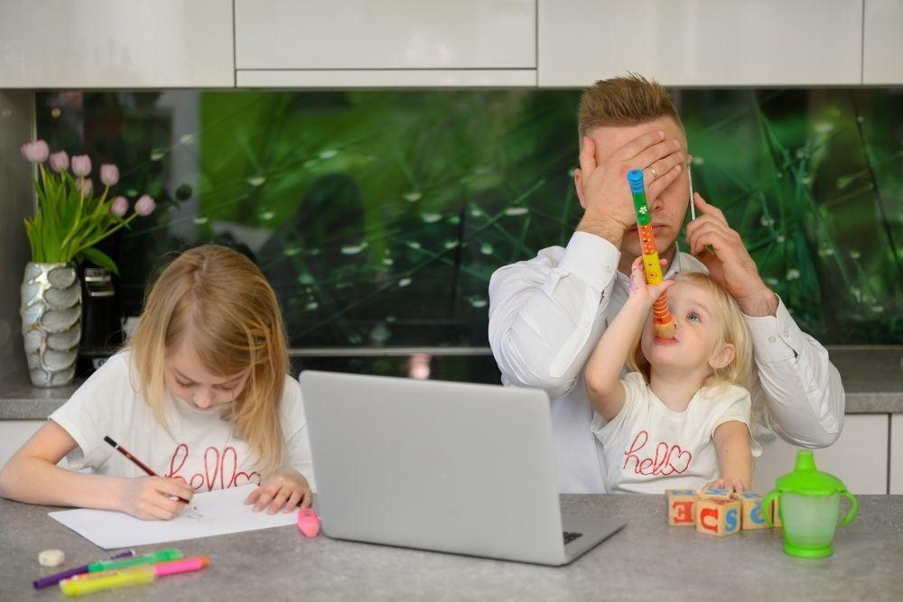 Stressaantunut isä yrittää tehdä töitä lasten ollessa paikalla.