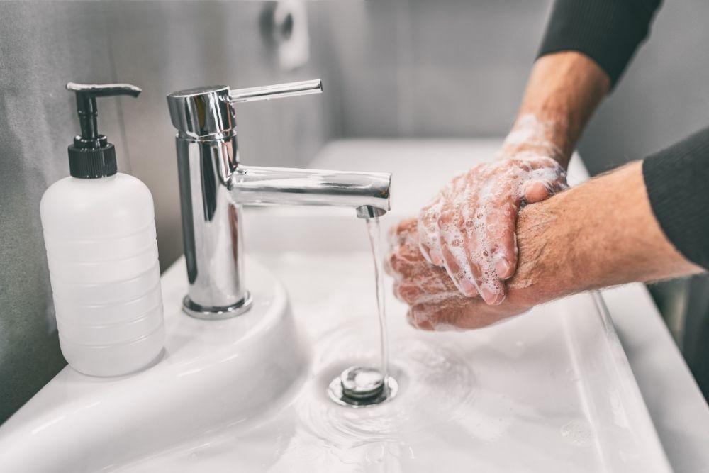 Mies pesee käsiään saippualla estääkseen koronan leviämistä.