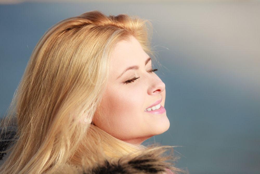 Nainen talvella auringossa ottamassa D-vitamiinia.