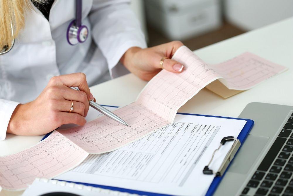 Lääkäri tutkii EKG-tulostaa löytääkseen merkkejä eteisvärinästä.