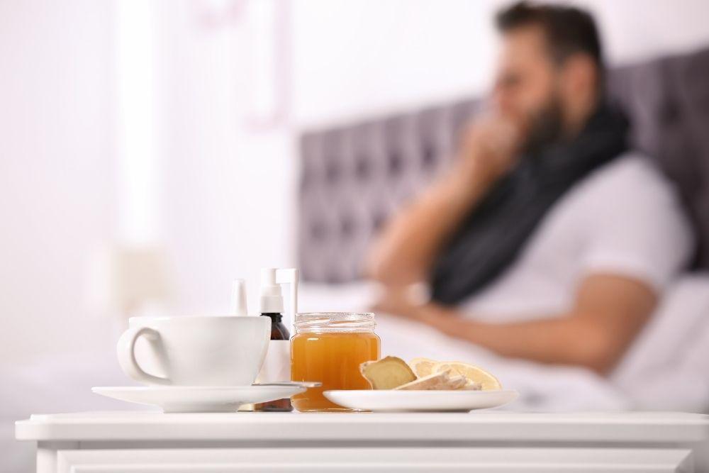 Influenssaan sairastunut lepää vuoteessa vieressään kuumaa juomaa ja hunajaa.