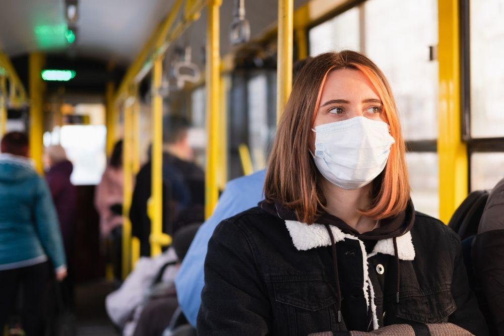 Nainen matkustaa korona-aikaan bussissa maski naamallaan.