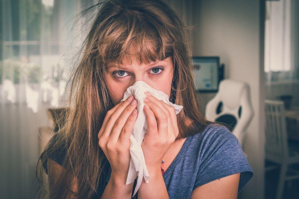 Flunssassa oleva nainen niistää nenäänsä.