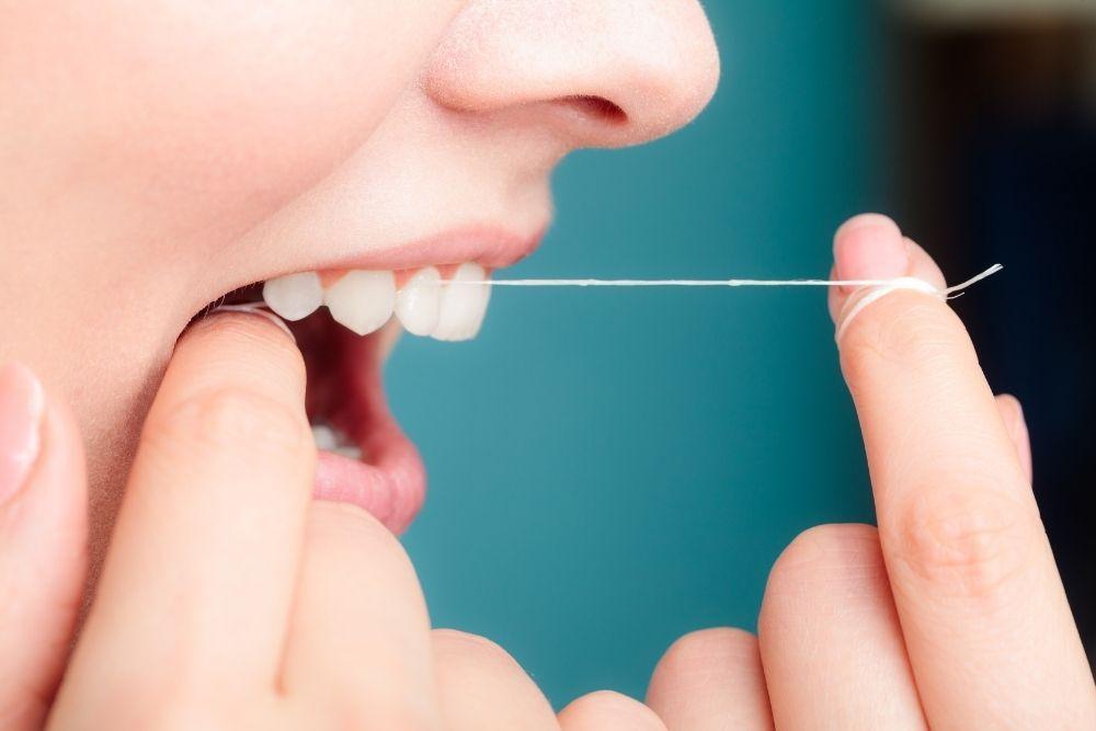 Nainen käyttää hammaslankaa hammaskiven ehkäisemiseksi.