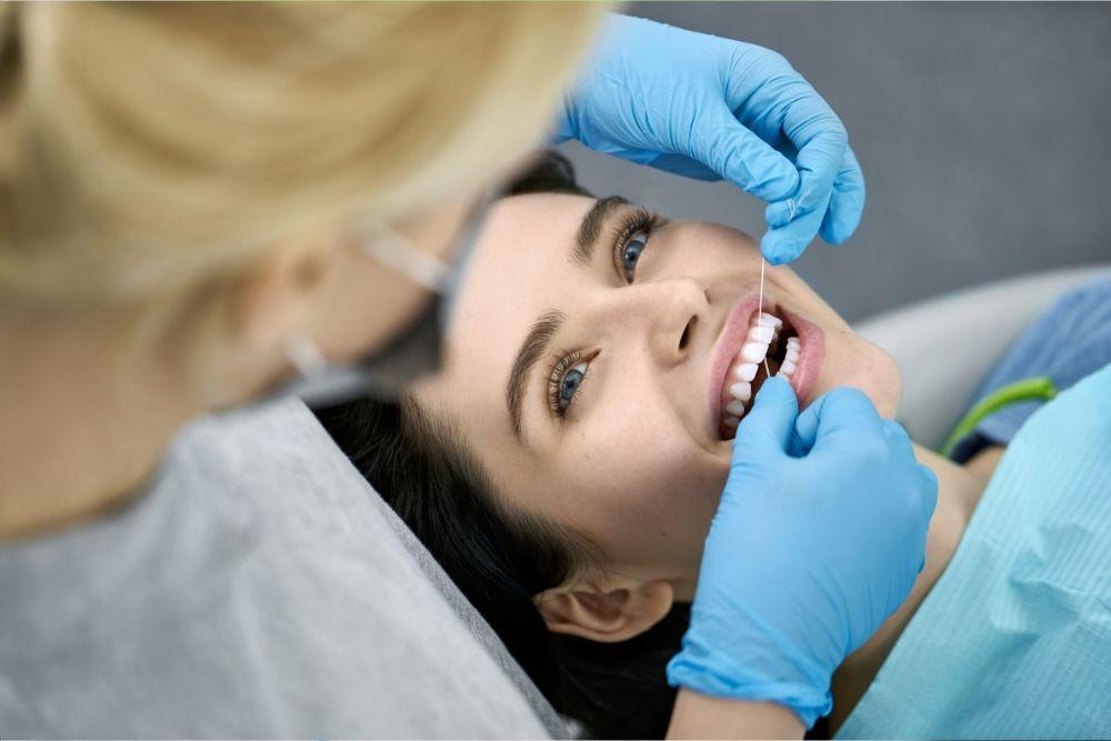Hammashoitaja puhdistaa hammaslangalla naisen hammasvälejä.