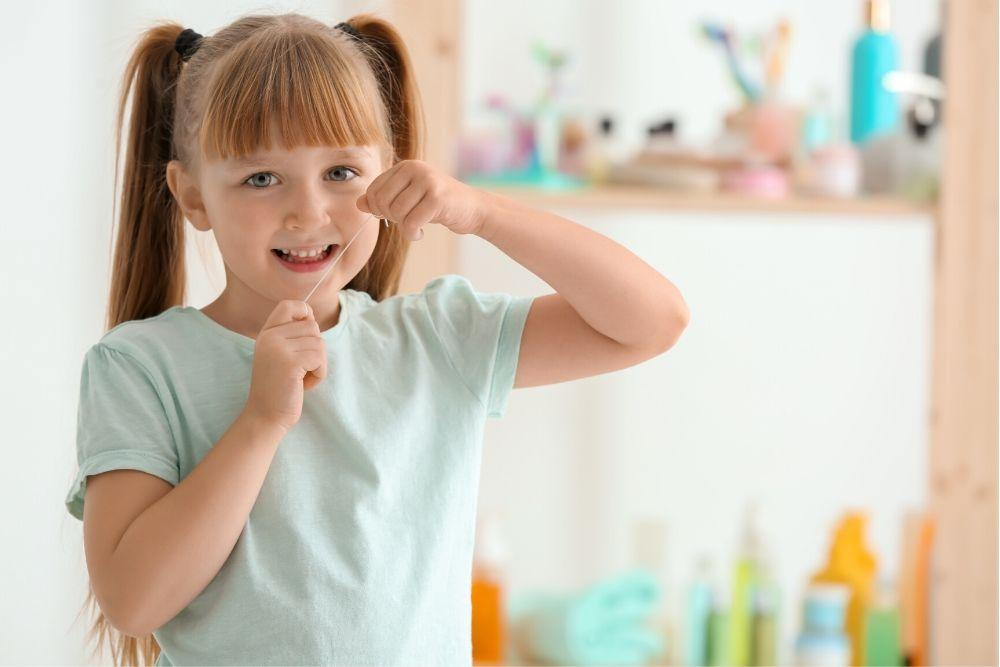 Ekaluokkalainen tyttö käyttää hammaslankaa.