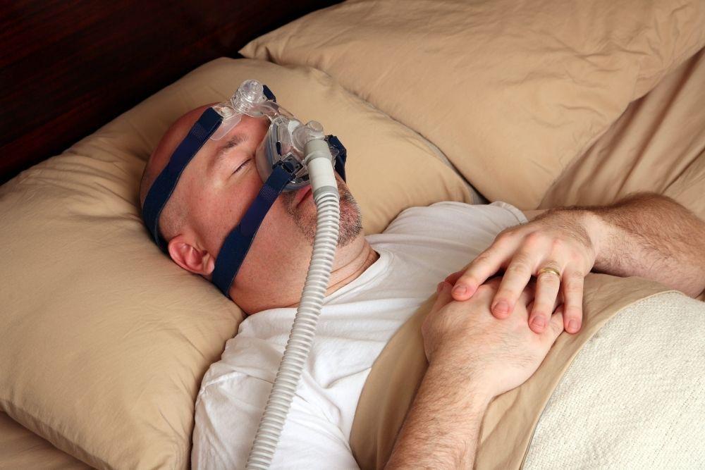 Uniapneasta kärsivä mies nukkuu CPAP-laite naamallaan.