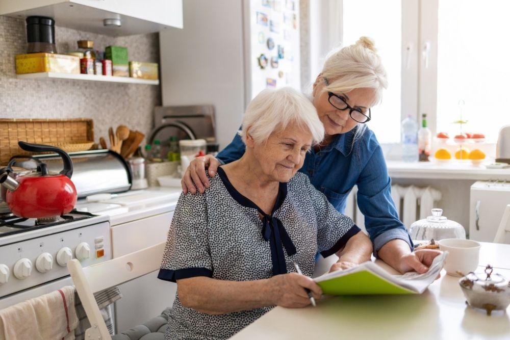 Valkohiuksiset äiti ja tytär lukevat papereita.