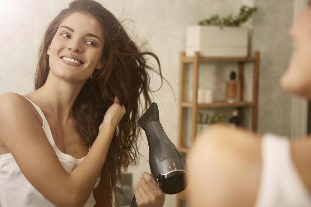 Nainen kuivaa hiuksia hiustenkuivaajalla