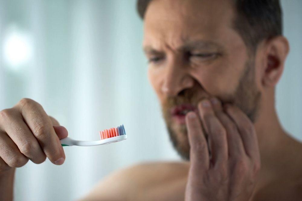 Mies pesee hampaita, hammasharjassa verta ientulehduksen vuoksi.