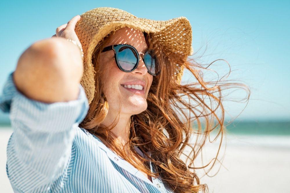 Nainen suojaa ihonsa hatulla ja aurinkolaseilla rannalla.