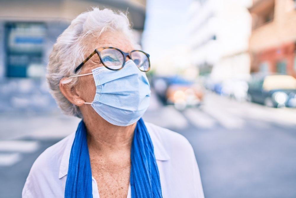 Kirurginen suu-nenäsuojus iäkkään naisen kasvoilla