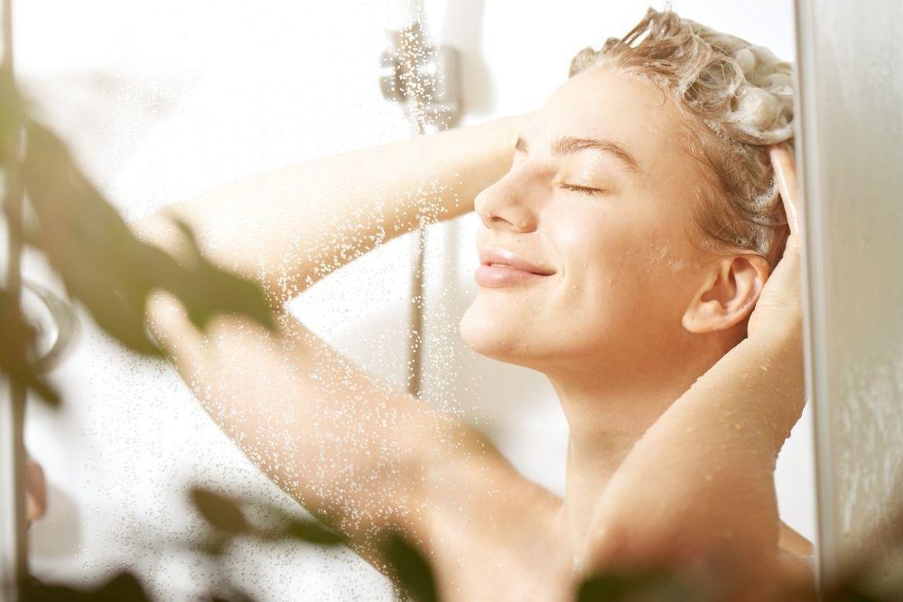 Nainen pesee kauniita hiuksiaan suihkussa.
