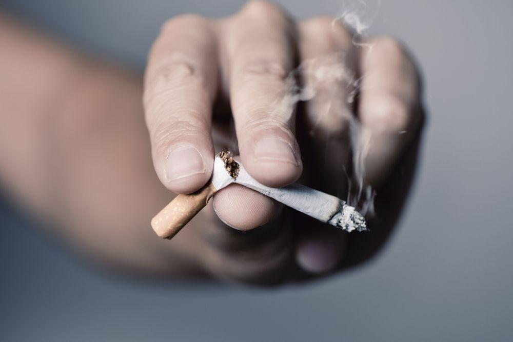 Katkaistu tupakka kädessä.