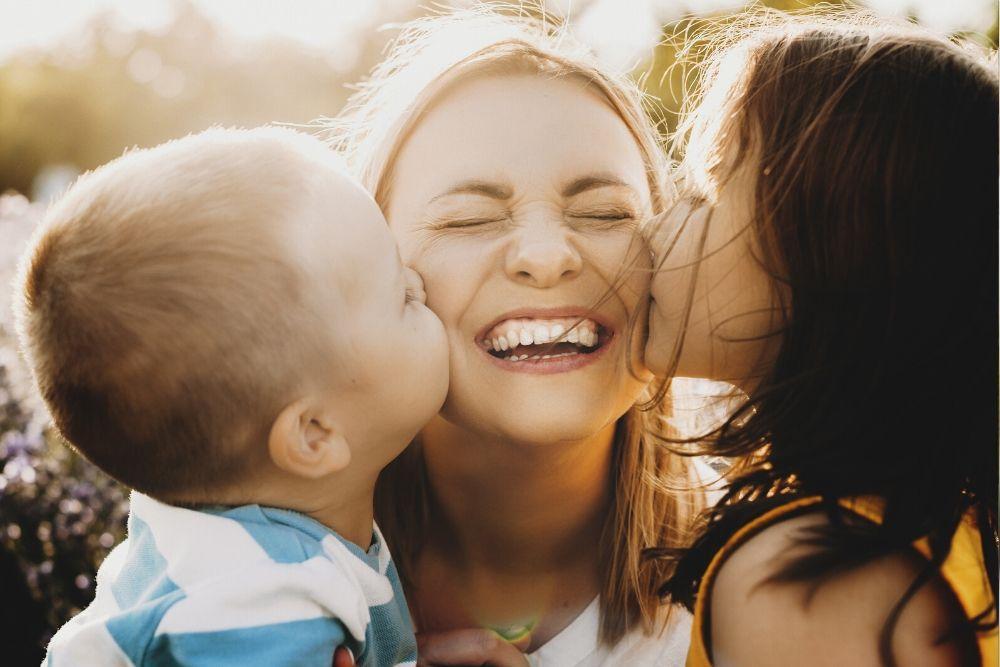Nainen hymyilee ja saa lapsilta pusut poskille.