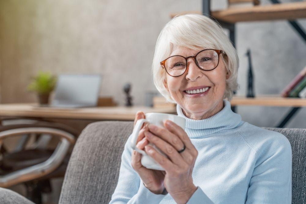 Ikääntyvä nainen istuu sohvalla muki kädessään.