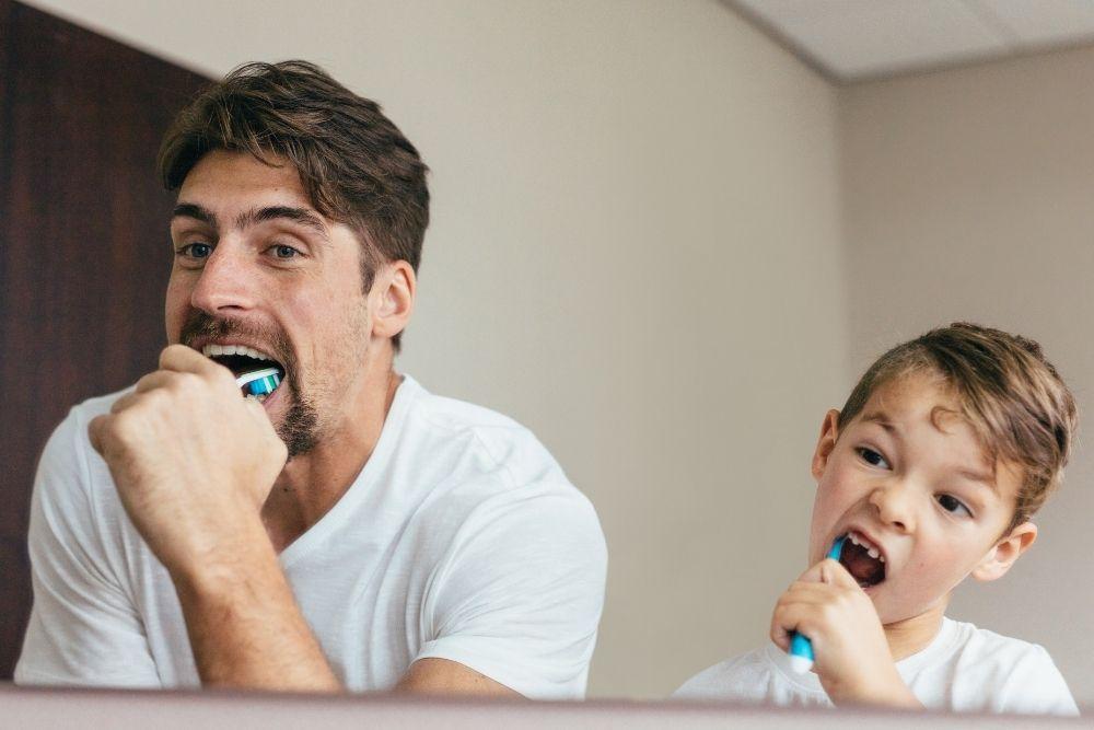Isä ja poika pesevät hampaitaan parodontiitin ehkäisyksi