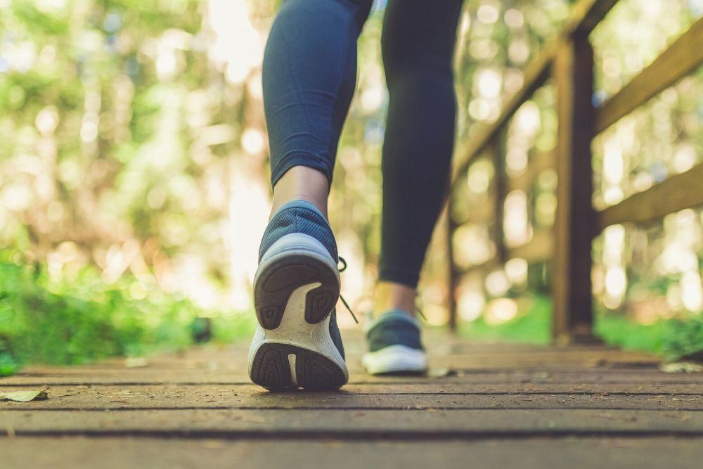 Lenkkarijalkaisen naisen jalat metsäpolulla.