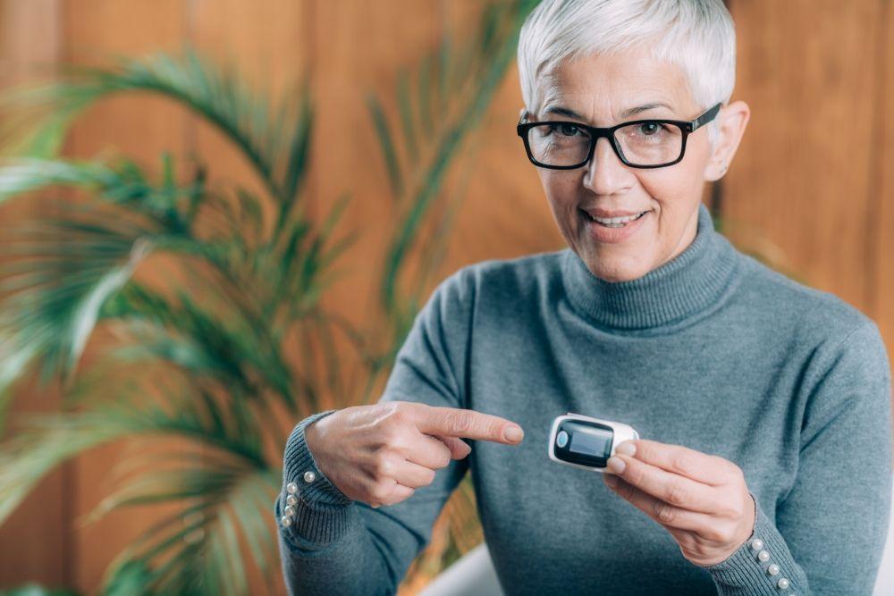 Nainen laittaa pulssioksimetrin sormeensa.