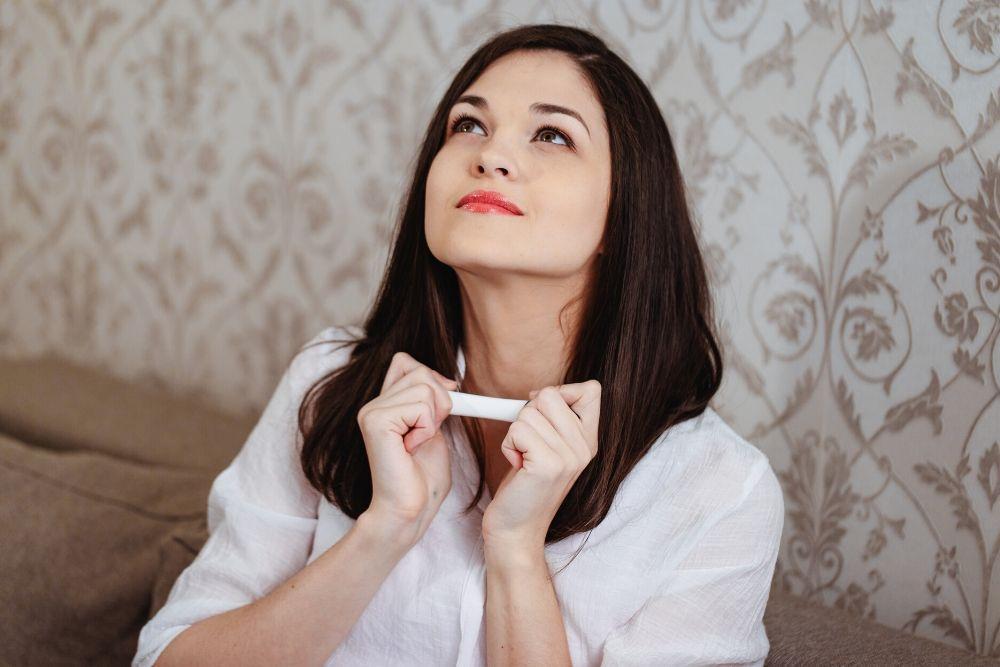 Nainen pitää raskaustestiä kädessään.