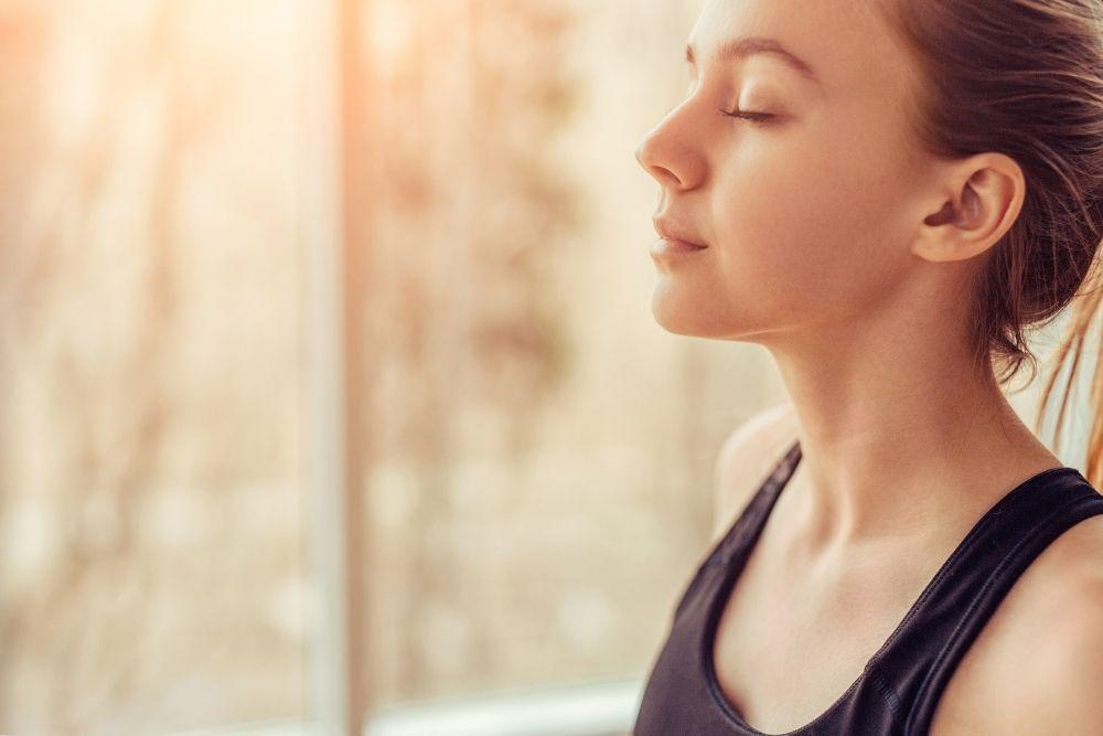 Nainen hengittää rauhallisesti stressin keskellä.