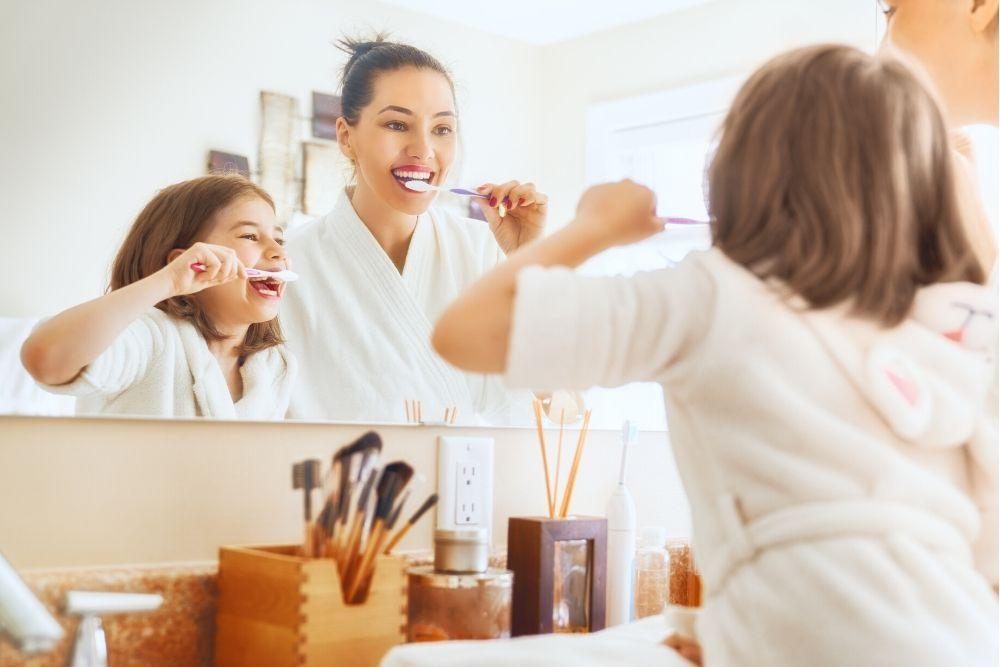 Nainen ja lapsi harjaavat hampaita ennen suuveden käyttöä.