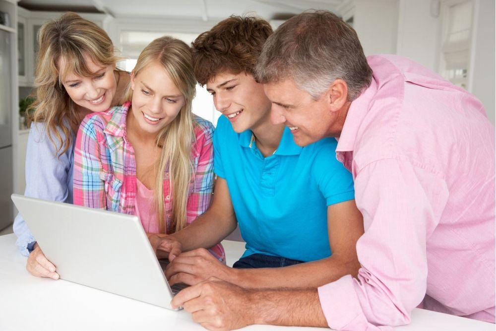 Perheenjäsenet katsovat tietokonetta lähekkäin toisiaan.