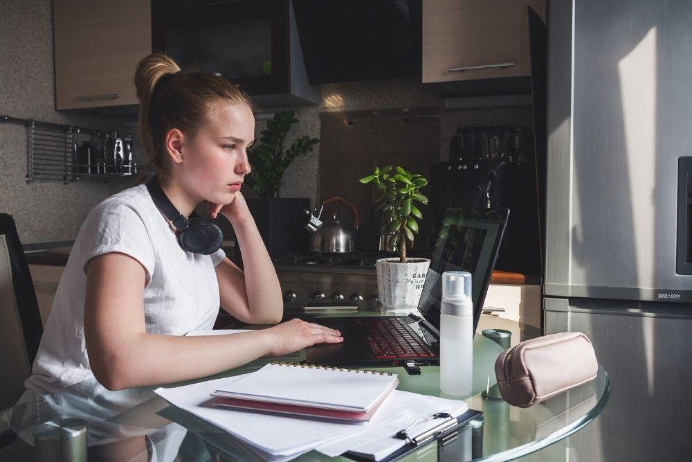 Nainen istuu työkoneen ääressä, aiheuttaa vatsan turvotusta.