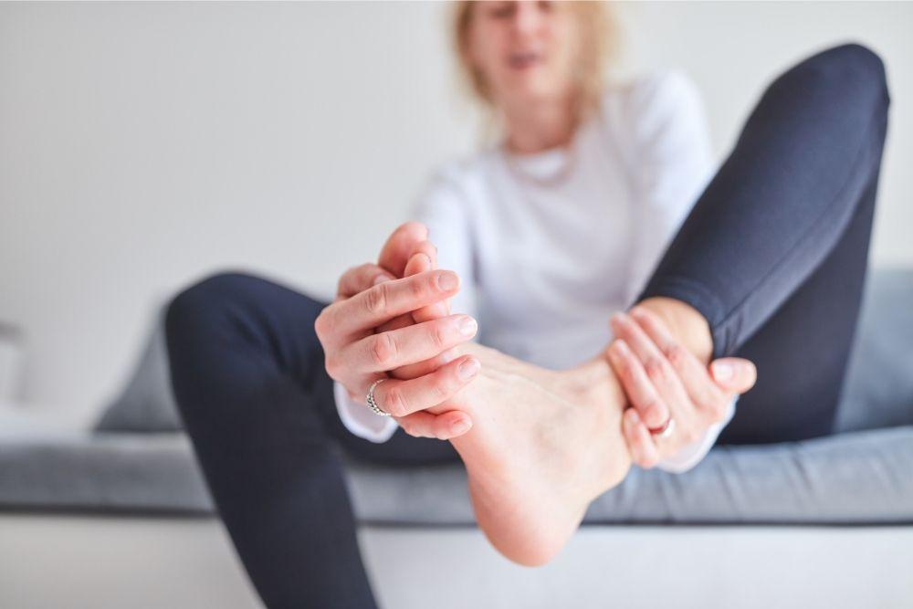 Nainen venyttää jalastaan kramppia pois